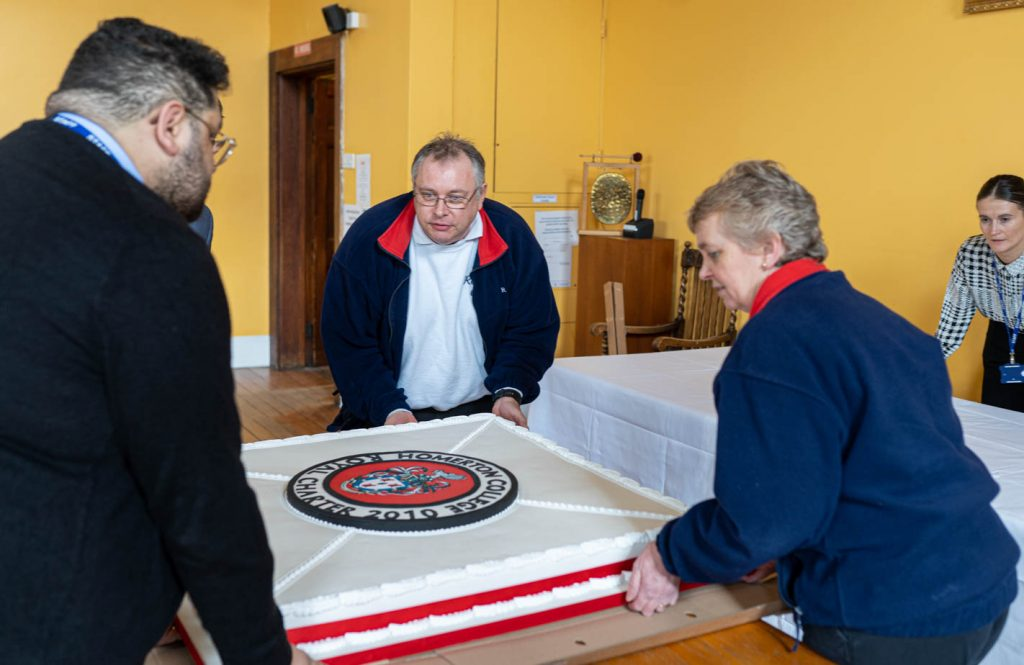 Graham and Rachel Farnham unboxing a metre square cake at Homerton College ready for display