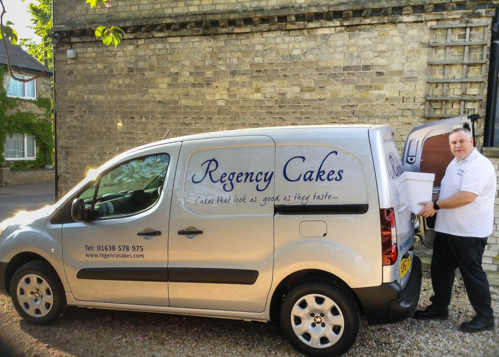 Graham Farnham loading a cake into the Regency Cakes van for delivery to a customer