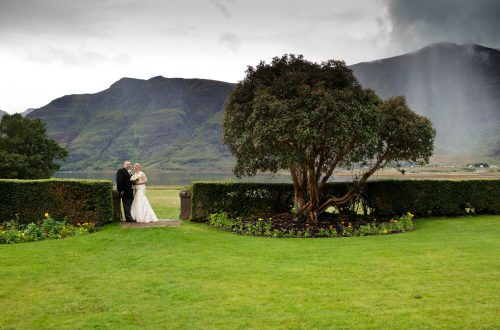 Bride and Groom stood overlooking Loch Torridon with mountains and tree